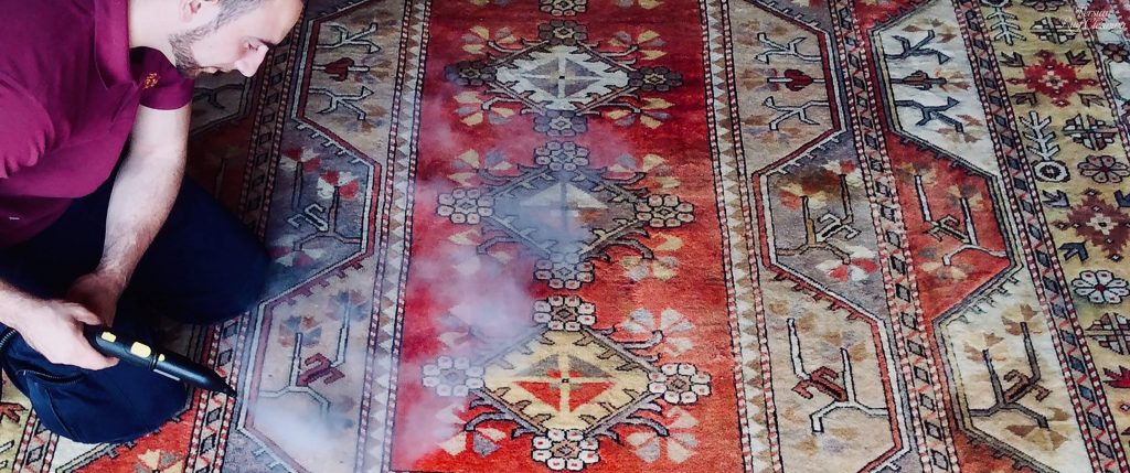 Das performing a colour restoration on a Turkish Melas rug